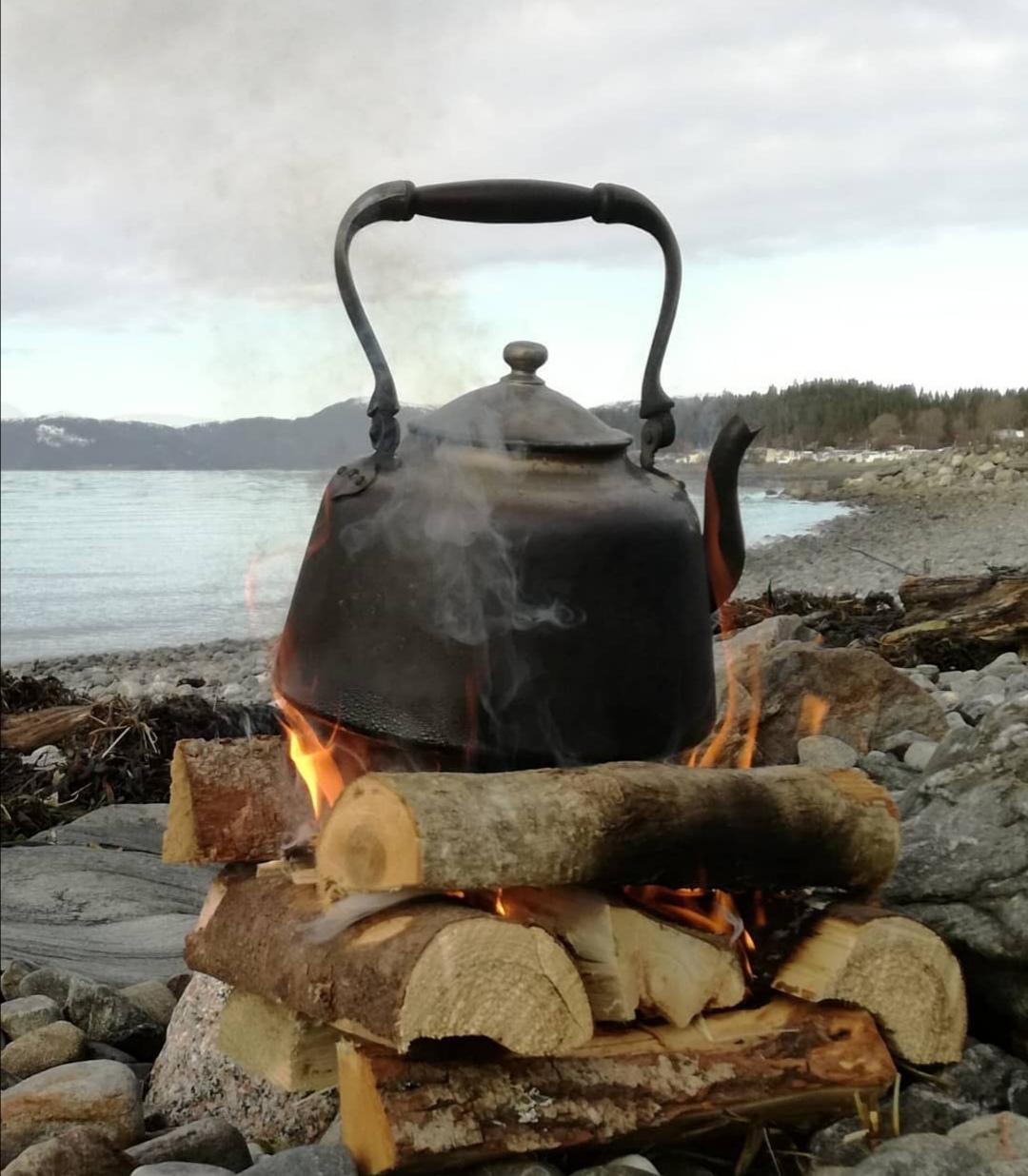 Teekessel auf Feuer am Flussufer
